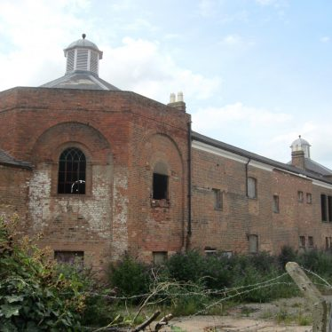 Red brick 2-storey building looking dilapidated with slate roof and mini cupolas on top of the octagonal towers at either end | Anne Langley
