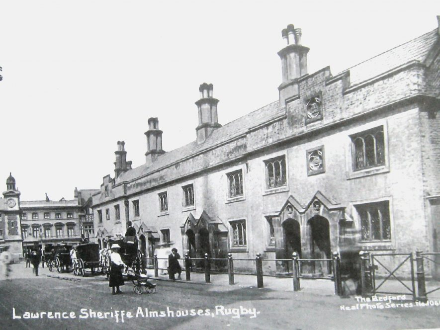 Stone row of 2-storey almshouses with gothic style windows and porches. Clocktower and Hackney cabs in the distance and a few pedestrians. | Warwickshire County Record office: PH352/152/128
