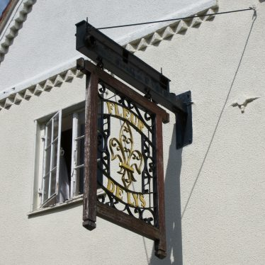 Sign with wrought iron fleur de lys attached to white painted pub wall | Anne Langley