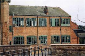 3-storey brick building with large green-painted windows (some broken and some boarded up) | Anne Langley