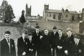 This photograph shows the first headteacher of Princethorpe College Father JK Fleming and pupils with the school buildings in the background. | Princethorpe College