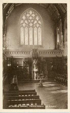 This photograph shows the interior of the chapel of St Mary's Priory, Princethorpe, looking at the carved masonry window in the west wall. | Princethorpe College