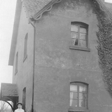 Stockton.  A woman and child outside a house