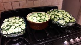 Sliced and salted cucumbers. Three large bowls stand on an oven range, full of cucumbers. | Image courtesy of Karen Moulder