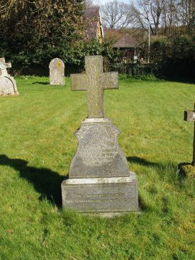 Cross over stone with inscription on in grassy churchyard. Other tombstones, trees and houses in the background | Image courtesy of Maureen Harris