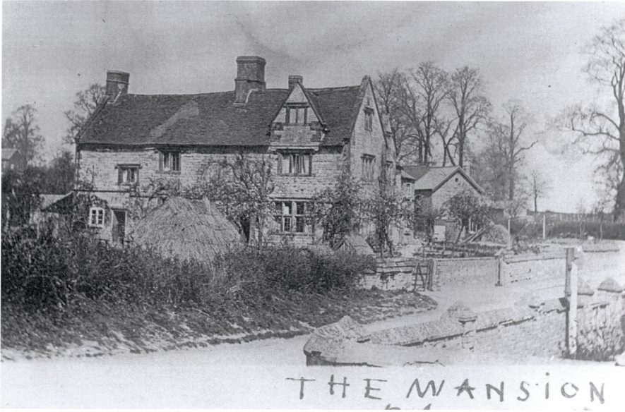 The Mansion, Bishops Itchington in the early 1900s. A back and white image of the house, which has a timber framed gable at the front right. beneath the image is written 'The Mansion' in pen. | Image courtesy of Bill Sutton