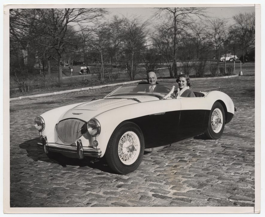An Austin-Healey 100M in a New York park. Donald Healey in the driver's seat and actress Louise King [wife of racing driver Peter Collins] in the passenger's seat. c.1955-1956.   Warwickshire County Record Office reference CR4804/3/132