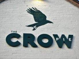 Crow Pie pub sign, Bilton, 2018. Flying black crow painted on white brick wall with title 'The CROW pie' on | Image courtesy of Anne Langley