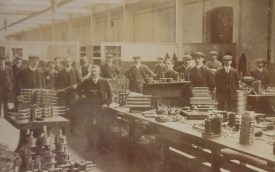 The View Room (motor) at the Humber Works, presumably at the then new Stoke plant. 1900s. Men stand behind some iron bars.   Warwickshire County Record Office reference PH352/65/64