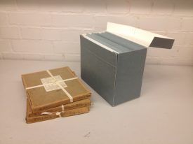 Glass plate negatives in original packaging and after being re-boxed. | Photo by Gary Collins.