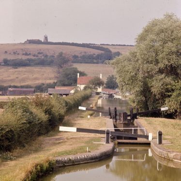 This view of the canal looking North, with the derelict Napton Windmill on the skyline, is almost identical to PH352/128/15 which was photographed in the 1910's. It is also almost identical to PH599/462, taken in the 1960's. the main difference is the loss of the trees on the skyline, the complete disappearance of the windmill sails and the addition of a brick-built bridge. | Reference PH1239/6/13