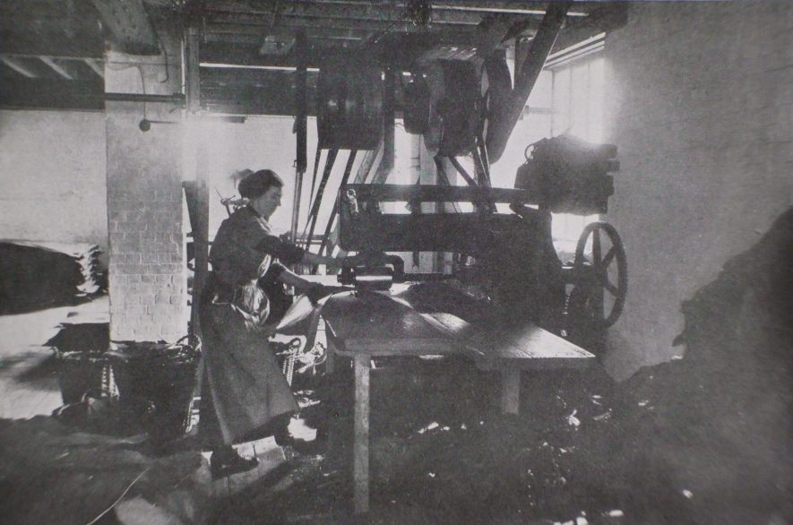 Woman standing at press, rolling leather by machinery. | Warwickshire County Record Office reference CR1520
