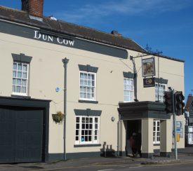Front of the Dun Cow pub at Dunchurch. 2-storey cream painted Georgian building with square porch and pub sign above | Anne Langley