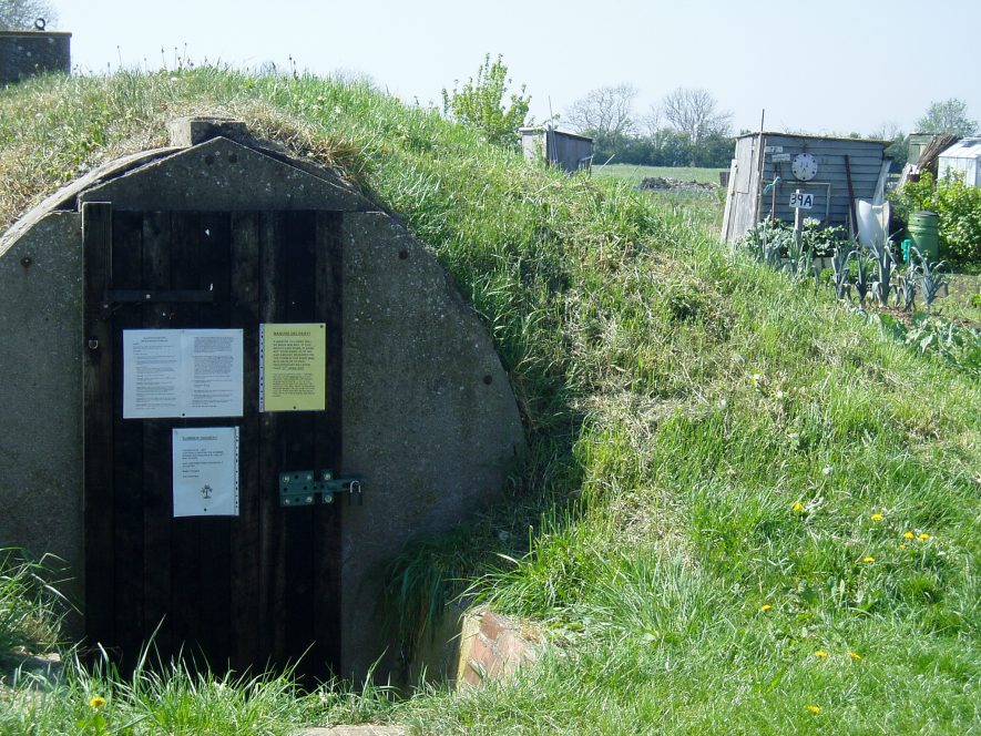 Tunnel-like building covered in grass with doors at the end uses as noticeboard, allotments with sheds in the background | Anne Langley