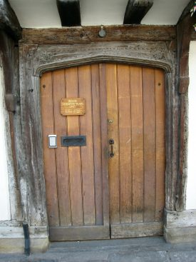 Wooden front door to the Church Street Almshouses, Stratford upon Avon. Plaque letter box etc. Timber framing visible above | Anne Langley