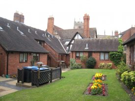 Back garden of Church Street Almshouses, Stratford upon Avon. Flower beds & dustbin store. Guild chapel tower in background | Anne Langley