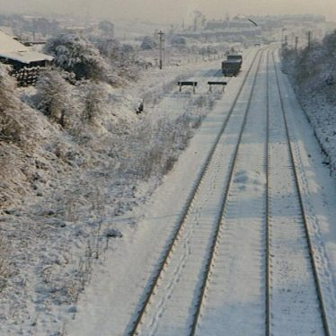 Haunchwood Brick and Tile Company's Sidings. A wintry scene with the Nuneaton-Birmingham line in the foreground. Looking back to Nuneaton. | From The Nuneaton Local History Group Collection. Photo by Geoff Edmands