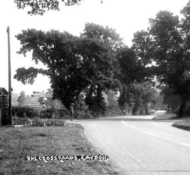 Elms by the crossroads near the Malt Shovel Inn. An AA patrolman is standing at the crossroads and an AA telephone box is to the left. 1950s. | Warwickshire County Record Office reference PH 226/123.