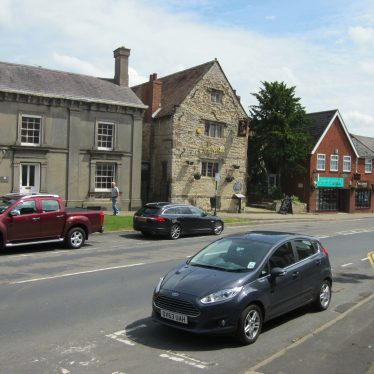 16th century stone building with several parked cars | Anne Langley