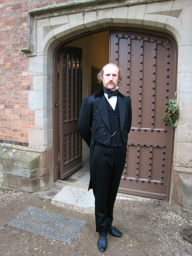 An actor dressed as a butler stands outside the kitchen door of Charlecote House in 2007. | Anne Langley
