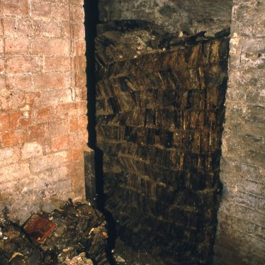 The cellar in which the collection was found, packed with negatives in a less than mint condition! There is a doorway and negatives piled from the ground up the walls. | Picture courtesy of the Warwickshire County Record Office, collection reference CR 2555