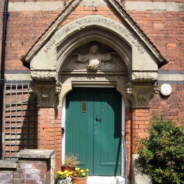 Steps up to a brick porch with carved stone text and religious statue over. Green painted wooden door and flower pots on the steps | Anne Langley
