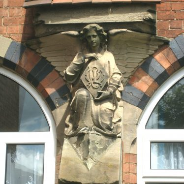 A carved stone kneeling angel, holding a lozenge with entwined initials, situated between two windows with decorative brick arches | Anne Langley
