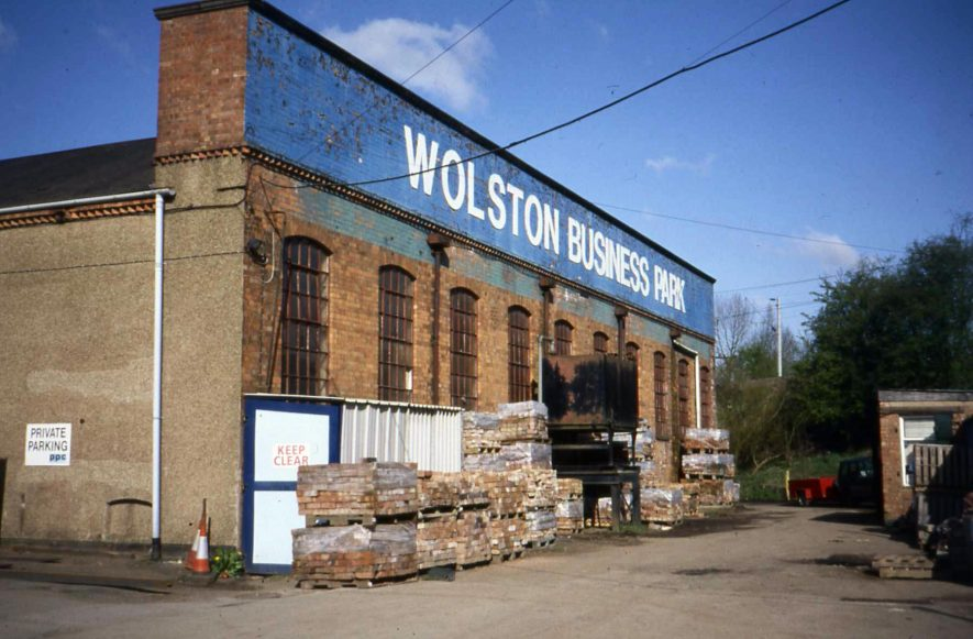 A red brick end wall of a factory headed 'Wolston Business Park' (white on a blue background). 1 storey high with 10 windows with iron cross bars. Side wall stuccoed (no windows visible). Dentilated brickwork detail at the top of the building. Pallets of goods stored along the end wall. | Anne Langley