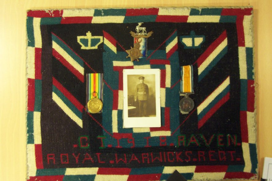 Tapestry commemorating Charles T Raven, Royal Warwickshire Regiment. Photograph, cap badge and 3 medals sewn onto the tapestry | Image supplied by Steven Frederick Jackman