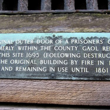 The caption on a metal plaque reads: 'Original outer door of a prisoners' cell formerly within the county gaol rebuilt on theis site 1695 (following destruction of the original building by fire in 1694) and remaining in use until 1861.' | Image courtesy of Anne Langley