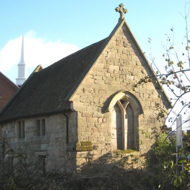 Small stone chapel with tiled roof with cross on top; simple tracery in pointed window on end wall and plain rectangular windows on side walls | Image courtesy of Anne Langley
