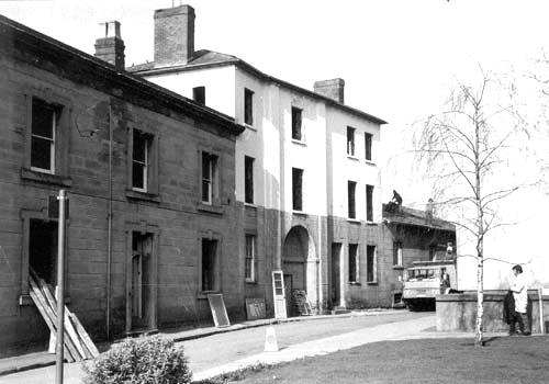 2 and 3-storey Georgian-style stone buildings. Workmen working on roof and building materials propped against the buildings.   Warwickshire County Record Office reference PH 143/57