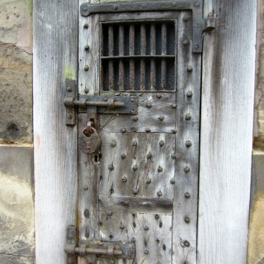 Studded wooden door with huge metal bolts, hinges and a padlock on the outside. It contains a small barred window. | Image courtesy of Anne Langley