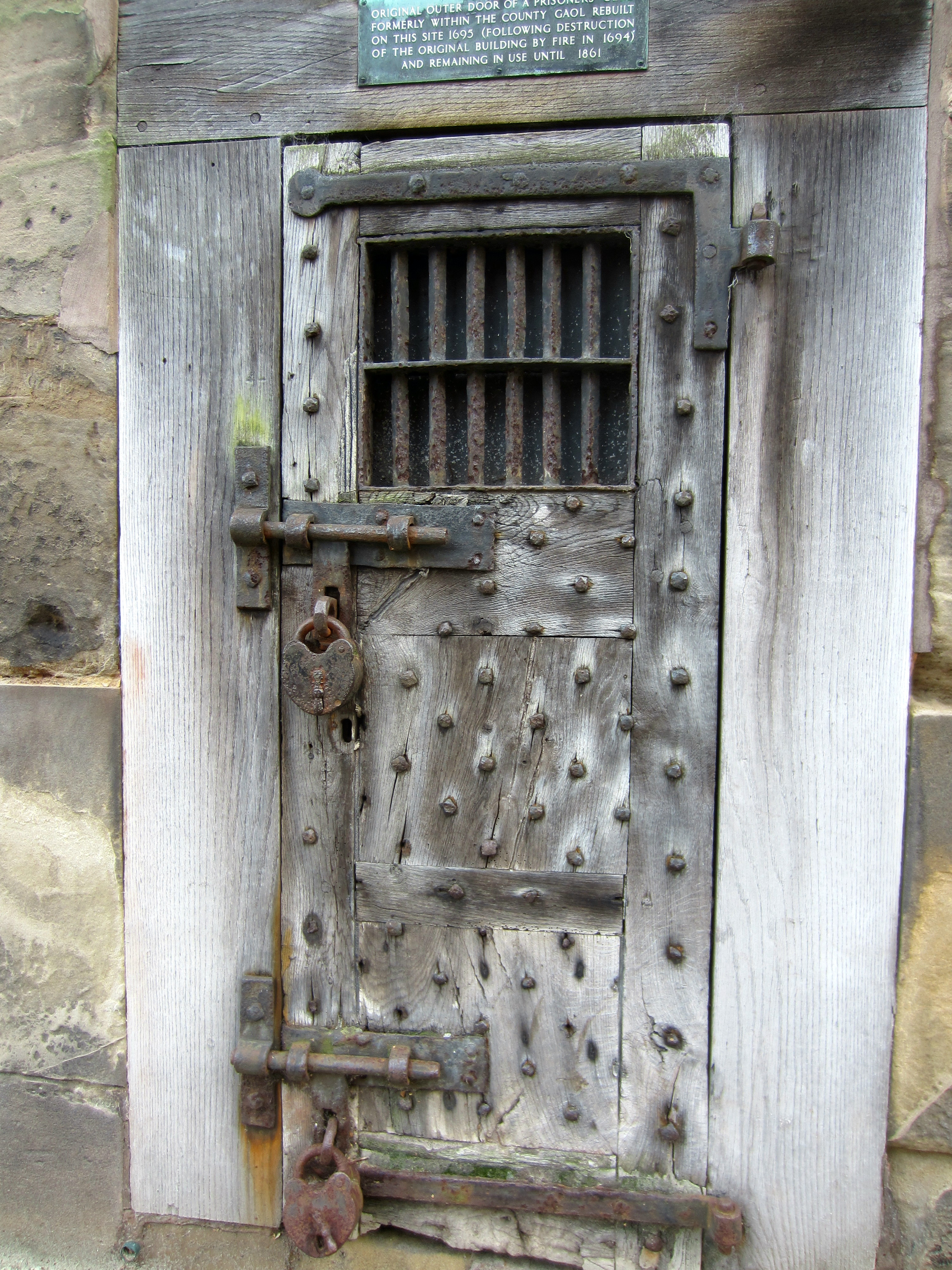 Studded wooden door with huge metal bolts hinges and a padlock on the outside. & Old Warwick Gaols - Our Warwickshire