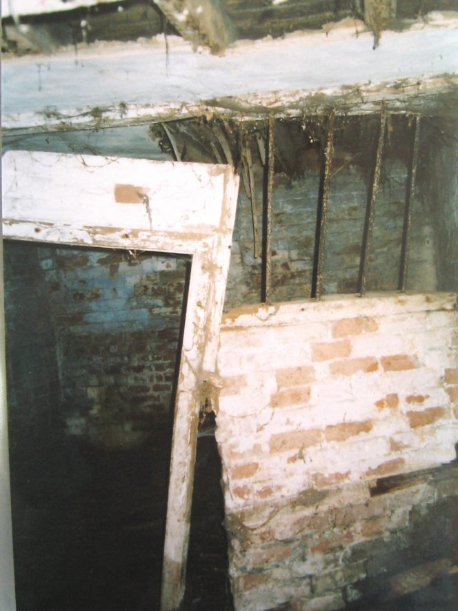 Brick walls and barred window, door disintegrating and roof beams exposed | Image courtesy of Anne Langley