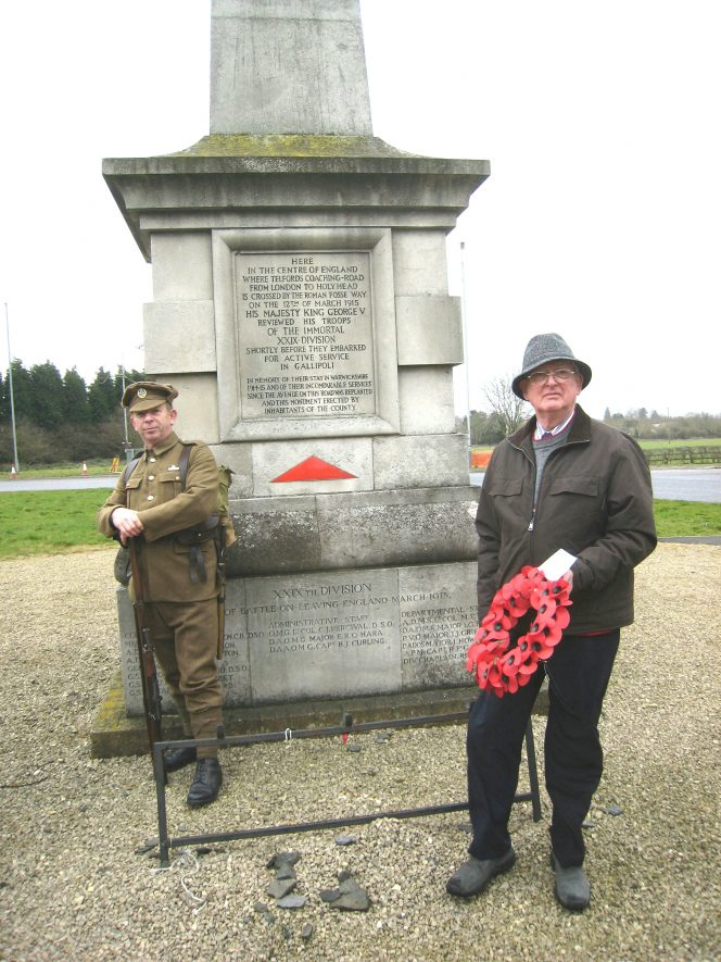 Man with poppy wreath, stone monument and a man dressed as a 1st World War soldier | Anne Langley