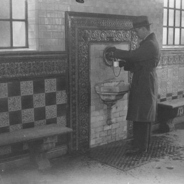 Interior of the Well House 1960. A man takes the waters from a chipped cup on a chain. | Warwickshire County Record Office reference PHN600/342/2
