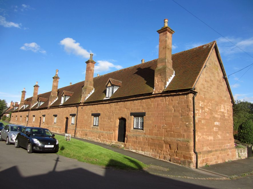 Row of 10 sandstone almshouses with tall chimneys and dormer windows in a tiled roof | Image courtesy of Anne Langley