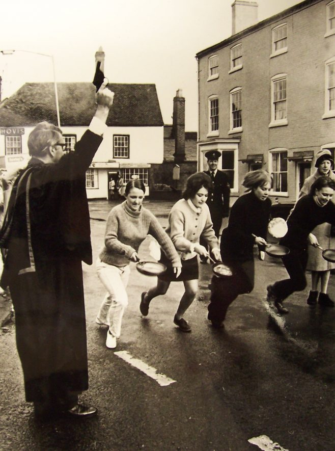 Pancake racing in Alcester, c.1971. Including schoolgirls and a girl tossing pancake with spectators. | Photograph copyright the Evesham Journal, and reproduced with their permission. Warwickshire County Record Office reference PH 1/119