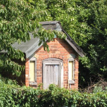 A small red brick summerhouse with wooden door and two windows, surrounded by foliage | Anne Langley