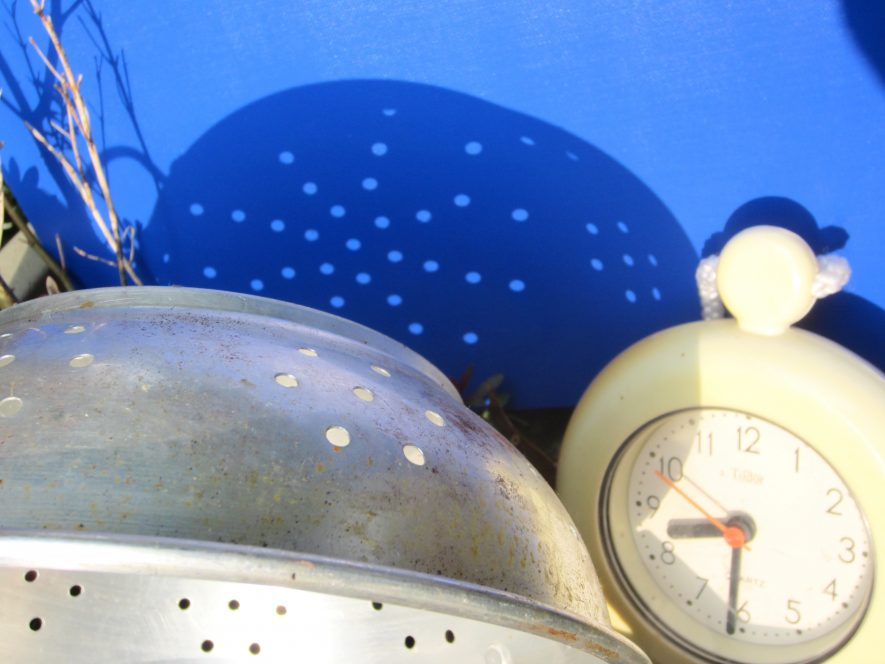 A colander casting a shadow with round images and a clock showing 8.30 a.m. | Anne Langley