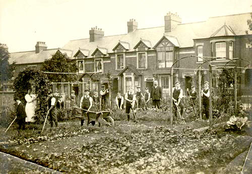 Vegetable garden with boys working with a wheelbarrow, hoes, forks etc. 3 adults (teachers?). Row of terrace houses behind. | Warwickshire County Record Office reference PH220/271