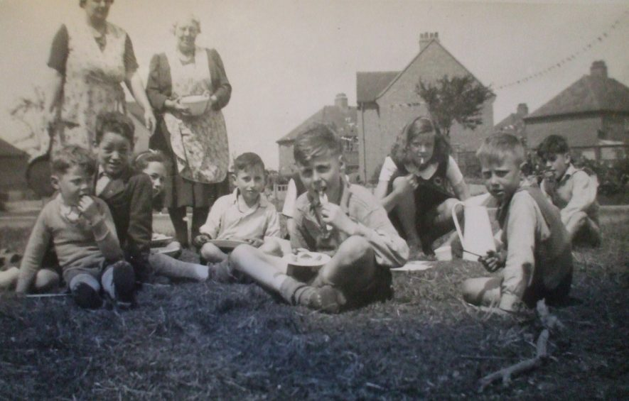 Our VJ Day picnic, Charter Avenue. I'm at the back right. A group of children gathered round a fire. | Picture copyright Doris Pails