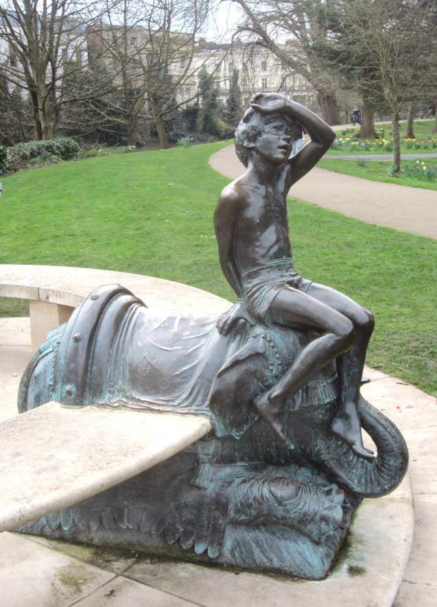 Circular seat interrupted by metal statue of boy sitting on an elephant. Daffodils in the background | Anne Langley
