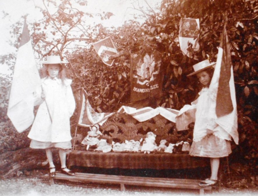 Photograph of two girls wearing straw hats with banners and dolls on bench [unknown identity] June 1897 | Warwickshire County Record Office, CR4651/529/1