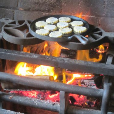 10 Welsh cakes on a griddle over an open kitchen fire