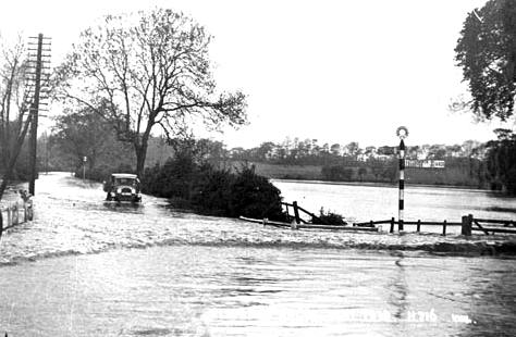 Van driving on flooded road near junction with signpost; flooded fields beside the roads and a telegraph pole. | Victor W Long; Warwickshire County Record Office reference PH 352/152/320