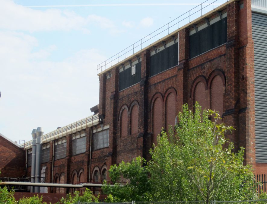 Red brick factory building with arched windows (blocked up) and modern additions | Image courtesy of Anne Langley