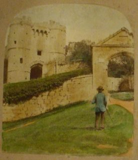 Carisbrooke Castle. A figure in a blue jacket, a hat and holding a walking cane approaches the entrance gate. | Image courtesy of Richard Neale.