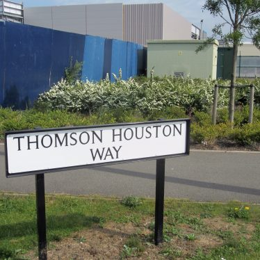 Metal road sign with landscaped garden, tree and modern factory buildings behind | Anne Langley